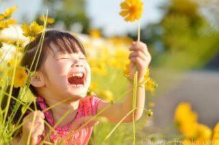 一眼レフカメラの単焦点レンズで撮影した花で遊ぶ女の子
